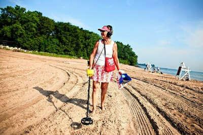 Поиск монет на пляже с металлоискателем