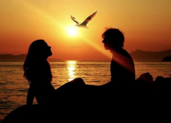 Душевно разговариваю с любимым мужчиной на берегу моря при закате.