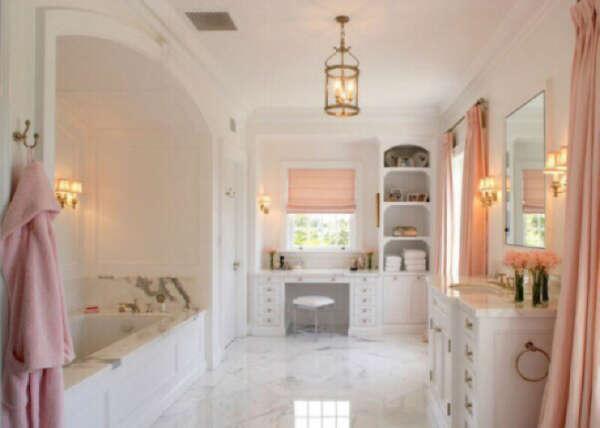 Просторная и тёплая ванная комната большой ванной, шикарной раковиной и туалетным столиком